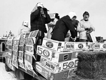 UCalgary students use empty beer cases to build a float on the back of a flat-bed truck at Stampede Park during the 1969 Bermuda Shorts Day