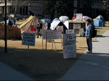 A student stops to read signs at a tent city set up outside MacEwan Hall by students protesting tuition hikes, 1999.